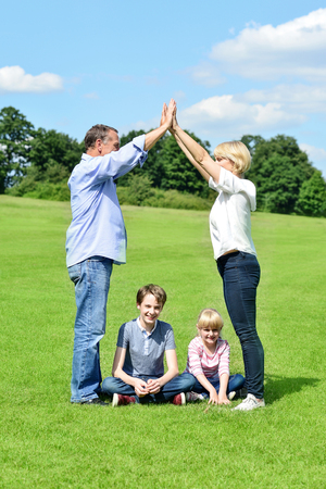 Parents playing game with children in field photo