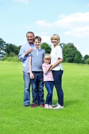Happy family of four standing together on the meadow photo