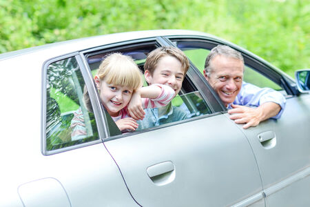 Father with his kids posing from car looking out windows photo