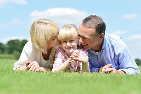 Happy parents lying and kissing their daughter in park photo