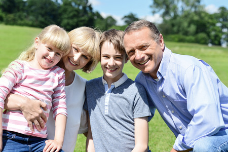 Happy family posing with two children at outdoors photo