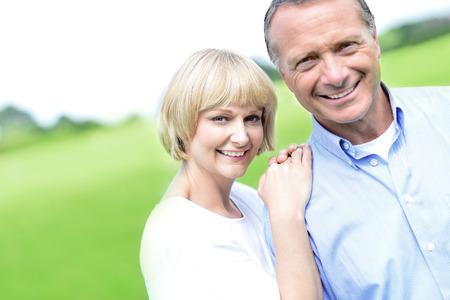 modelos posando: Feliz pareja de mediana edad posando juntos en el exterior