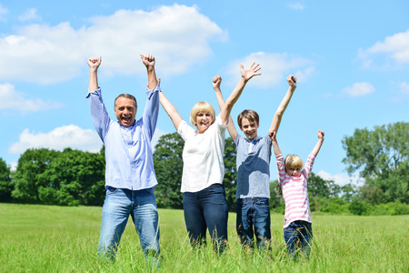 Cheerful family of four lifting arms up in the air photo