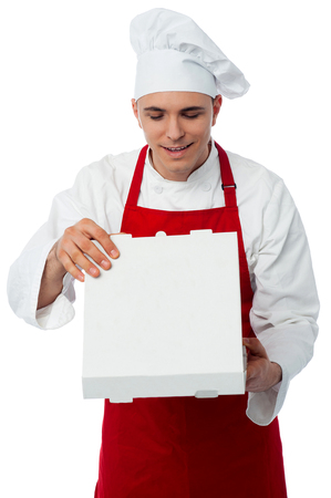 Smiling male chef opening pizza box, isolated on white photo