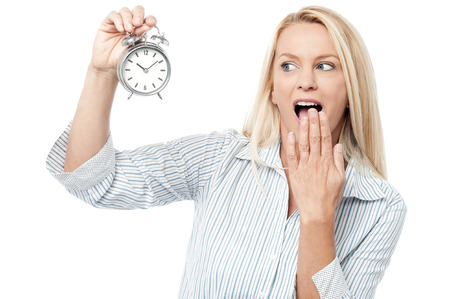 Middle aged woman shocked and holding alarm clock photo