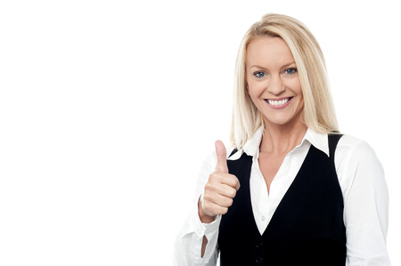 posing  agree: Smiling business executive making thumbs up gesture