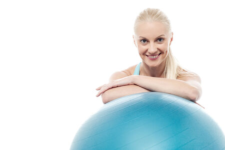 Fit lady relaxing after workout beside exercise ball Stock Photo