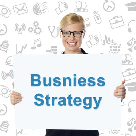 business strategy: Smiling businesswoman holding business strategy banner Stock Photo