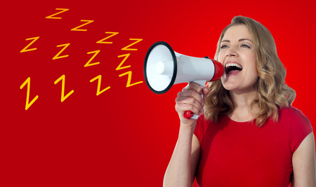Attractive woman loudly speaking into a megaphone photo