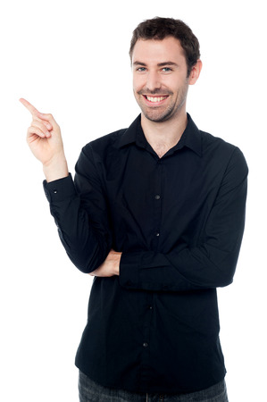 facing away: Guy pointing away while facing camera Stock Photo
