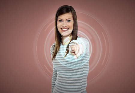 Beautiful woman pointing her finger on virtual screen photo