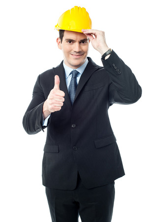 posing  agree: Happy architect with hardhat showing thumbs up gesture Stock Photo