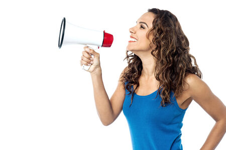 making an announcement: Young woman making announcement with a megaphone