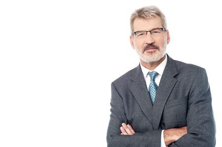 Glimlachend oude zakenman stellen met gekruiste wapens Stockfoto
