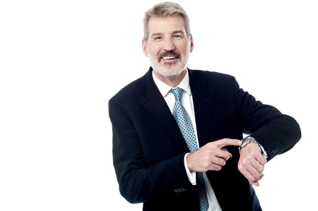 Businessman pointing time on his wrist watch