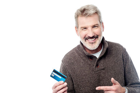 Mature man holding and pointing out his credit card photo