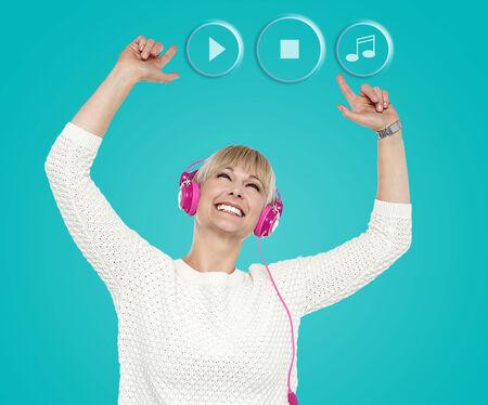 Woman enjoying music with hands raised photo