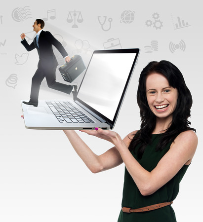 Businessman running out of a laptop screen for his business photo