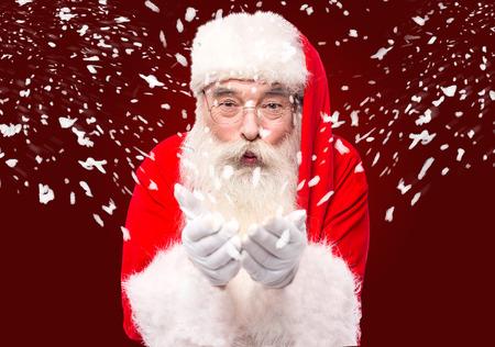 saint nick: Santa Claus blowing playing with snow and enjoying Stock Photo