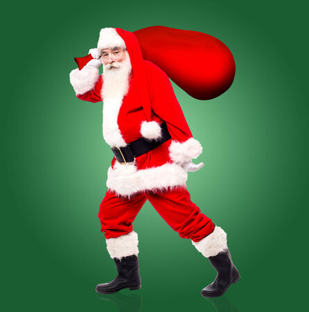 saint nick: Santa claus walking away with gift bag to distribute the gifts Stock Photo