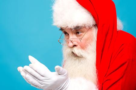 saint nick: Santa Claus showing something in his hands