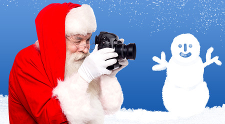 saint nick: Santa taking a picture of snowman at winter Stock Photo