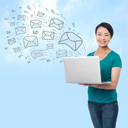 e pretty: Pretty woman sending e-mails from a laptop, sky background Stock Photo
