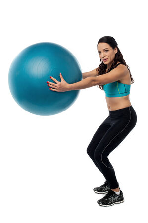 swiss ball: Young woman exercising with a swiss ball