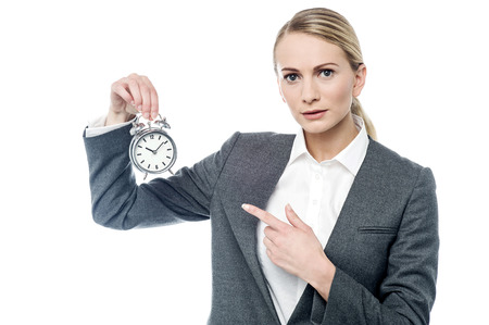 Female manager pointing at the alarm clock Stock Photo