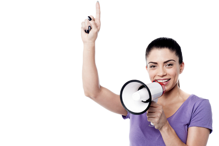 making an announcement: Happy woman making announcement over a bullhorn Stock Photo