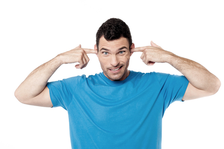 plugging: Casual young man plugging ears with fingers