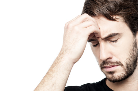 Frustrated man thinking deeply, hand on head.