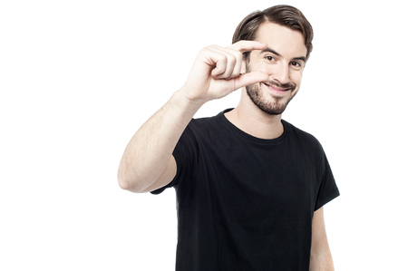 amount: Casual man showing small amount gesture Stock Photo