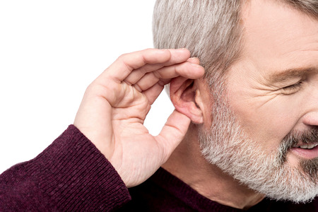 Aged man holds his hand near ear and listening