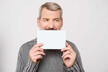 Casual mature man holding up business card photo