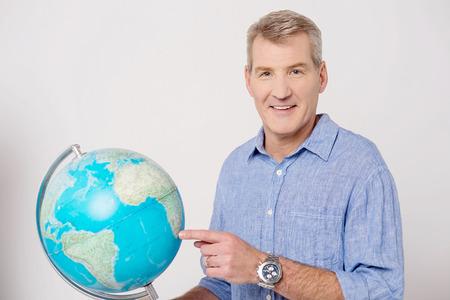 Senior man holding globe and pointing photo