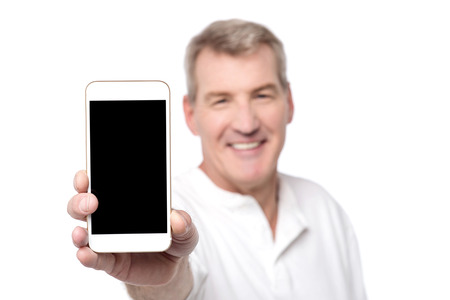 Happy senior man showing his mobile to camera Stock Photo