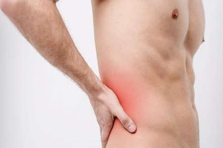 reddening: Shirtless male holding his back for the pain