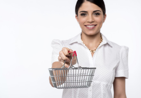 young add: Woman showing small shopping cart, focus on shopping cart
