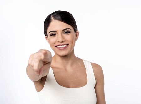 outwards: Smiling woman pointing her finger outwards