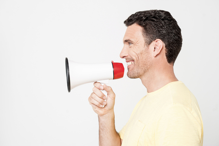 loudhailer: Sideways of man proclaiming into the loudspeaker