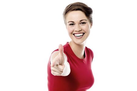 finer: Mujer alegre que se�ala su m�s fino para usted Foto de archivo