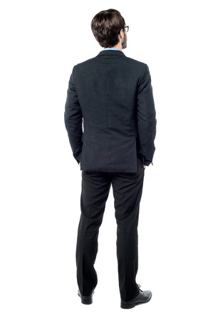 back pocket: Full length of businessman facing the wall