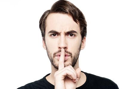 ? ?  ? �silence: Hombre joven con el dedo en los labios pidiendo silencio Foto de archivo