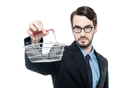 worried businessman: Worried businessman showing small shopping cart