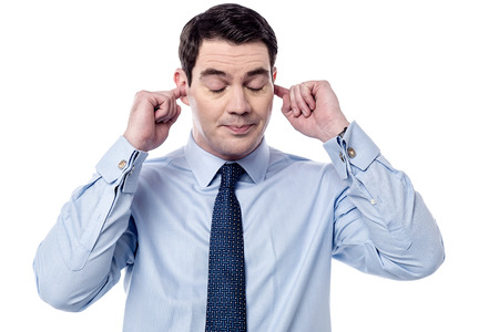 Businessman plugging ears with fingers