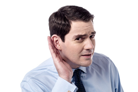 Businessman holds his hand near ear, listens closely. photo