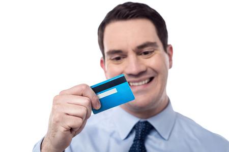 debit card: Smiling corporate man looking his new debit card