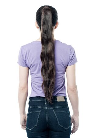 facing a wall: Casual woman facing the wall, from back. Stock Photo