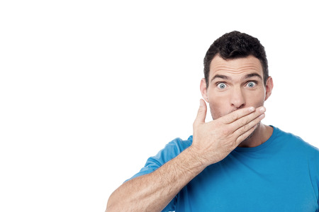 covering mouth: Casual man covering his mouth with hand over white Stock Photo